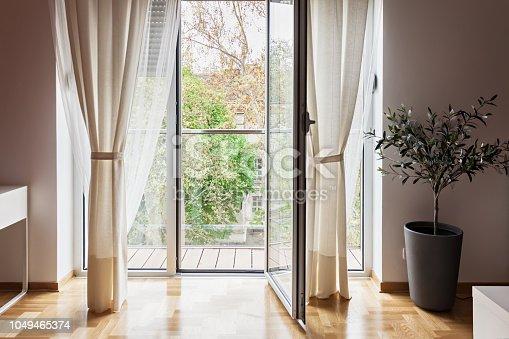 istock Modern apartment view through open terrace door 1049465374