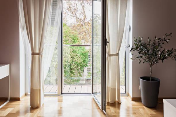 modernes apartment blick durch die offene terrassentür - fensterdeko herbst stock-fotos und bilder
