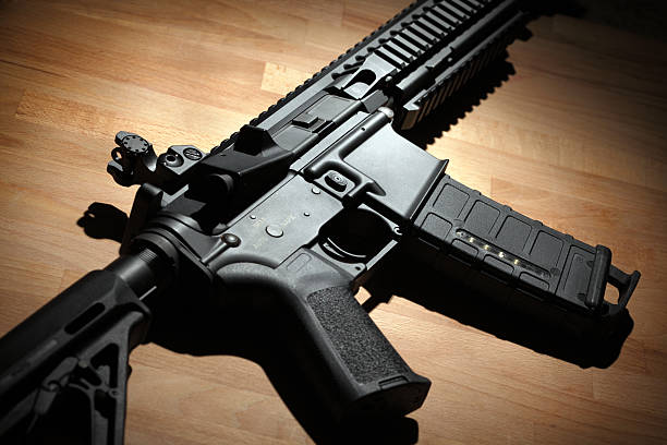 Modern AR-15 (M4A1) carbine Modern custom AR-15 (M4A1) carbine on a wooden surface. Studio shot ar 15 stock pictures, royalty-free photos & images