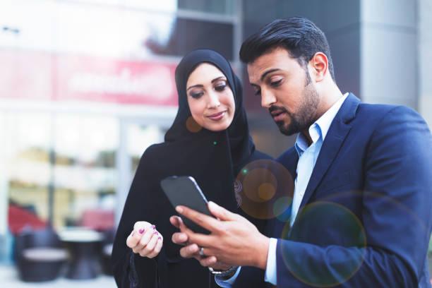 在他的智慧手機上顯示他的妻子線上消息的現代阿拉伯丈夫 - emirati woman 個照片及圖片檔