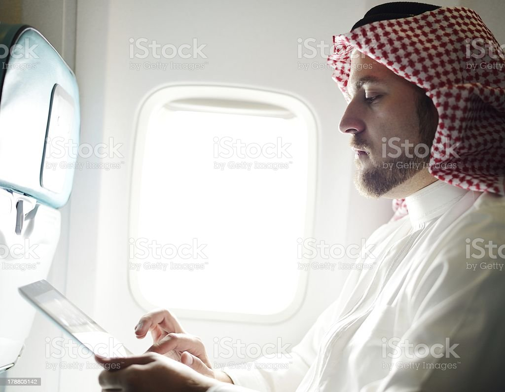 Modern Arabic businessman inside airplane using tablet stock photo