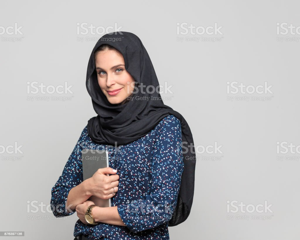 Modern arabic woman with digital tablet Portrait of beautiful muslim woman holding digital tablet and looking at camera. Businesswoman in hijab standing against grey background. 20-29 Years Stock Photo