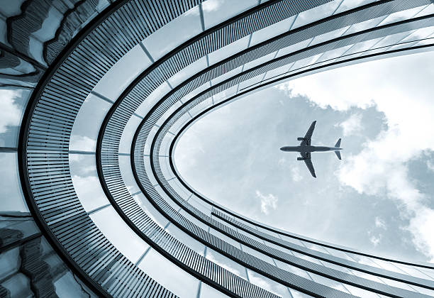 Modern architecture building with landing airplane stock photo
