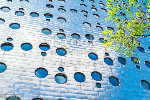 The modern facade of the Dream Downtown Hotel with porthole windows and steel cladding in the Chelsea district of Manhattan, New York City, USA on a sunny day.