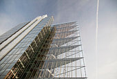 transparent modern architecture glass facade, triangular levels seem to float in front of an evening sky.