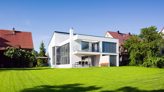 Modern Architecture Sustainable Green Home Panorama with Summer Garden Meadow Front Yard under blue cloudless summer sky.