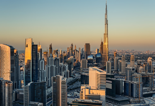 Beautiful modern city architecure at sunset. Rooftop view of Dubai's business bay towers.