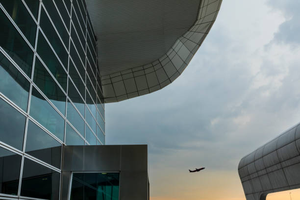 Modern architetural building with commercial airplane taking off At sunset time at Kuala Lumpur International Airport, commonly named KLIA, a commercial airplane take off in the horizon, with nice reflection on the glass modern architecture of the buildings. kuala lumpur airport stock pictures, royalty-free photos & images