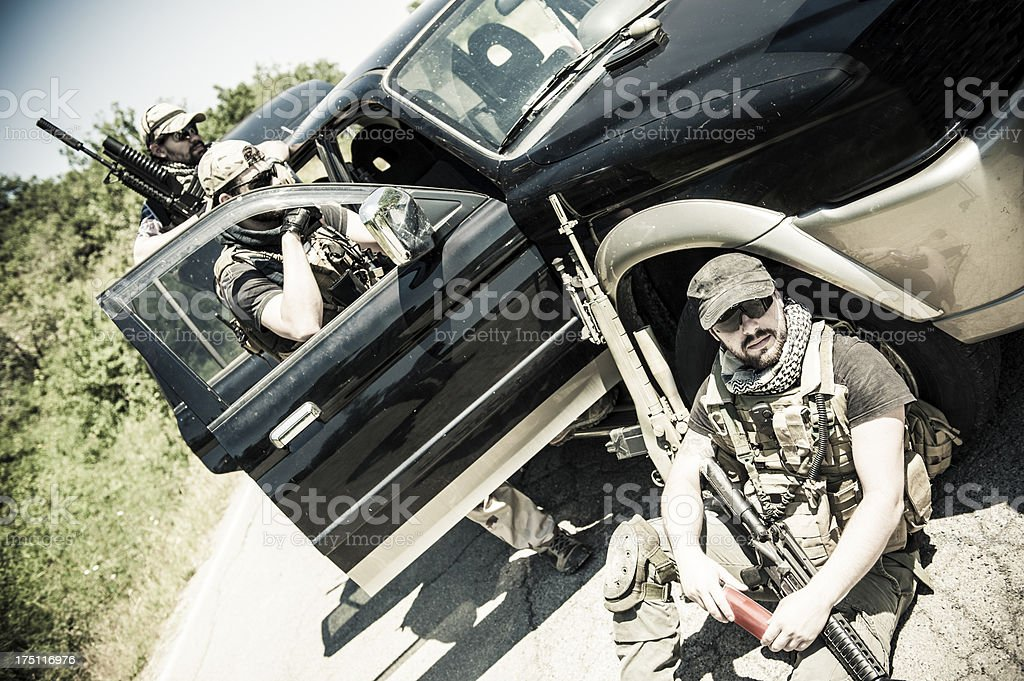 Modern Army Mercenary Soldiers Guarding a Roadblock with Car royalty-free stock photo