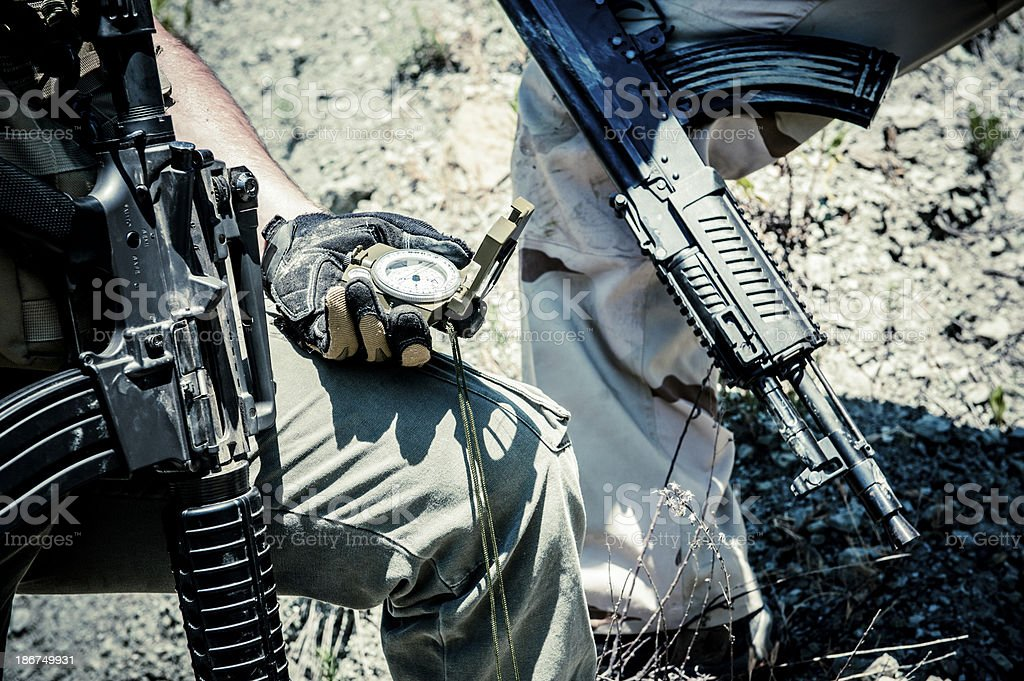 Modern Army Soldiers with Assault Rifles Orientating Using Compass stock photo