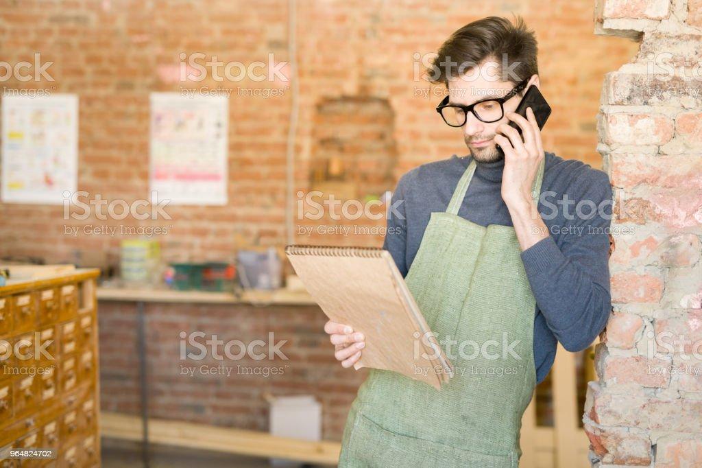 Modern Artisan Speaking by Phone royalty-free stock photo