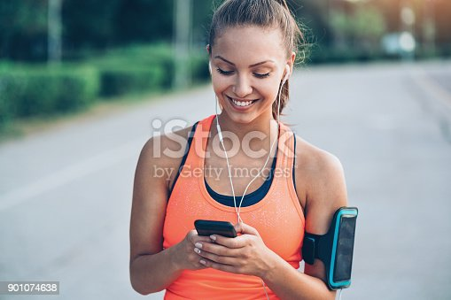 Young sportswoman texting on the street