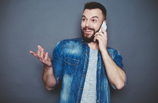 825083556 istock photo A modern attractive smiling man in a denim shirt speaks with his wife over the phone on a gray background. 910170374