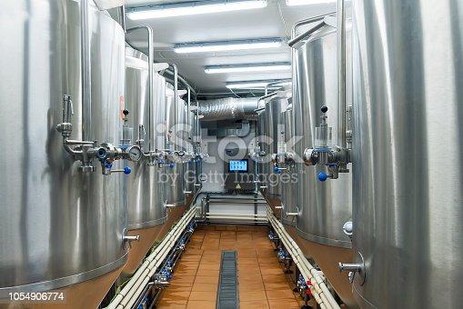 513948652 istock photo Modern automated beer factory. Lines of metal tanks in modern brewery. Shopfloor with brewery facilities. Manufacturable process of brewage. Inside view of modern beer plant with stainless barrels 1054906774