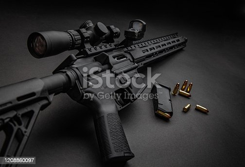 Modern automatic carbine with optical and collimator sight. A rifle with two sights on a dark background. Cartridges for weapons near a carbine.