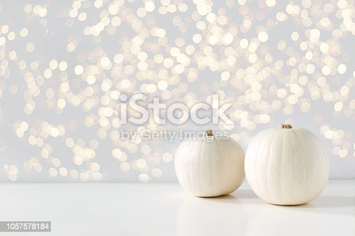 Modern autumn styled composition with white pumkins and golden sparkling bokeh lights. Halloween, Thanksgiving party concept, festive fall design.