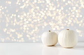 Modern autumn styled composition with white pumkins and golden sparkling bokeh lights. Halloween, Thanksgiving party concept. Festive fall design.