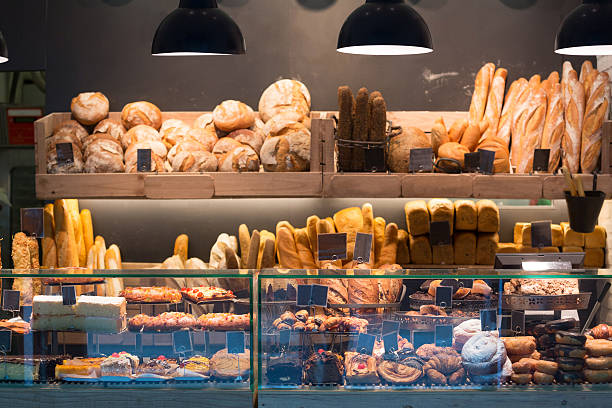 modern bakery with assortment of bread - bakeries stock photos and pictures