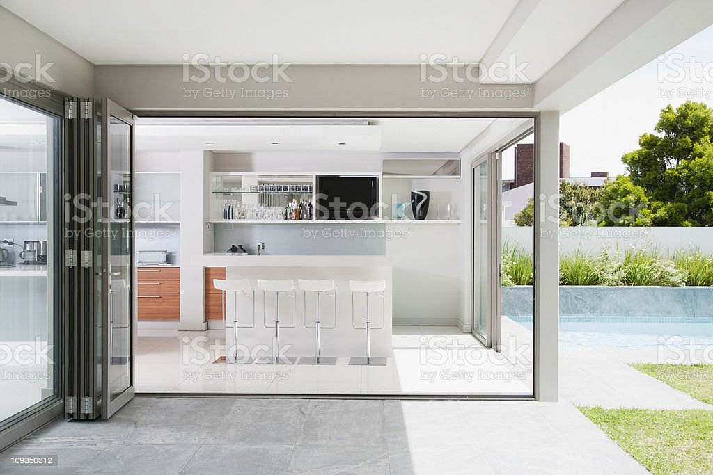Modern bar and barstools next to patio and swimming pool stock photo