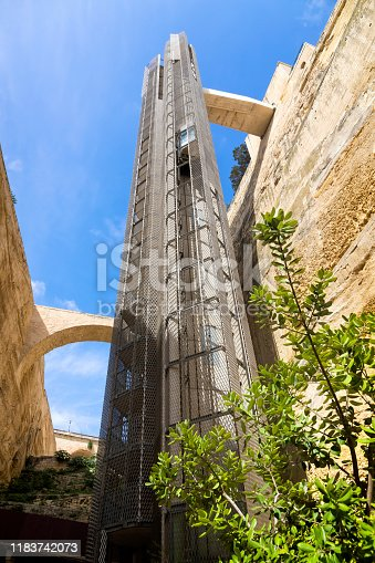 Modern barrakka lift built into historic walls below upper Barrakka gardens in Valletta, Malta