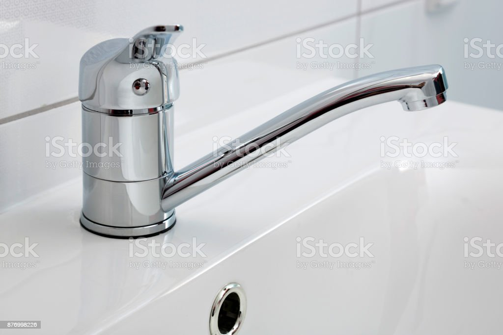 Modern bathroom faucet close-up installed on the sink stock photo