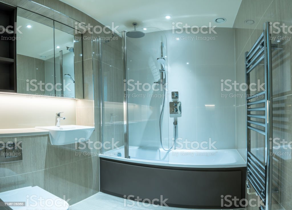 . Modern Bathroom In Apartment With Shower Bath And Tiled Surfaces