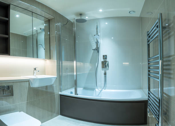 Modern bathroom in apartment with shower bath and tiled surfaces stock photo