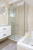 Master bathroom interior in luxury home with shower, and bathtub. Includes sink and tile floor.