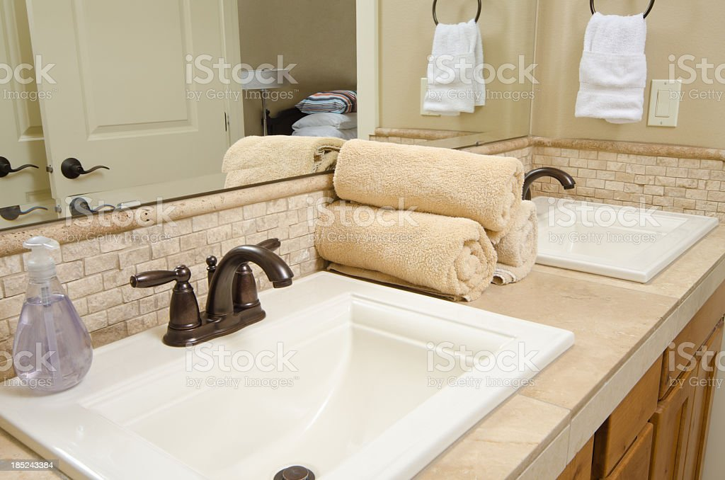 A modern bathroom sink with rolled up towels and hand soap stock photo
