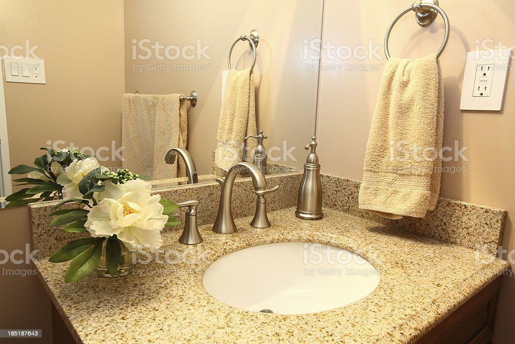 Modern bathroom vanity with beige granite top and faucets stock photo