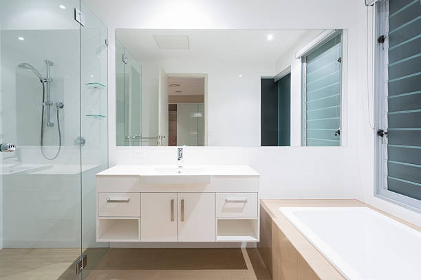 Modern bathroom view of mirror above sink and next to shower stock photo