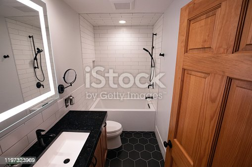 Modern bathroom design with matte black floor, matte black fixtures and deep soaking tub with lighted mirror.