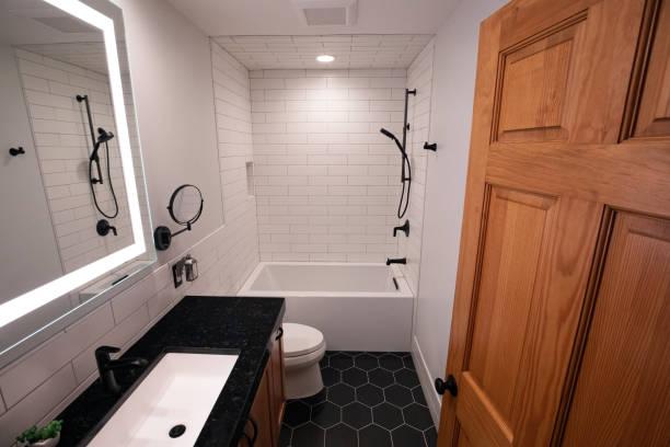 Modern Bathroom with Deep Bathtub and Black Hexagonal Floor Tiles and Matte Black Fixtures stock photo