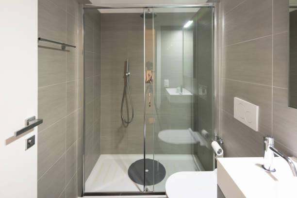 Modernes Badezimmer mit großen braunen Fliesen und großen Spiegel – Foto