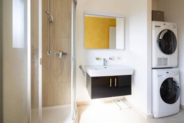 Modernes Badezimmer mit Dusche, schwarzem Waschbecken, Waschmaschine und Trockner – Foto