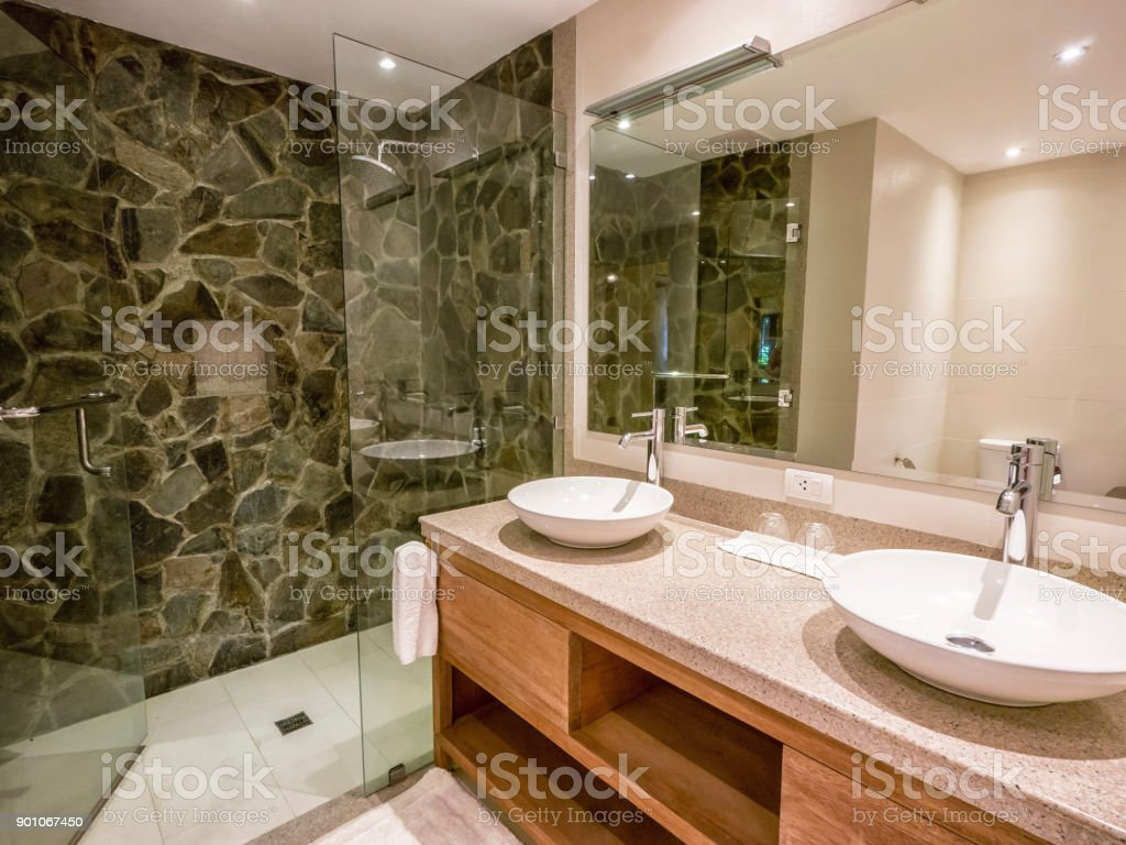 Modern bathroom with two round, white vessel sinks on granite counter. Natural stone and glass shower enclosure. stock photo