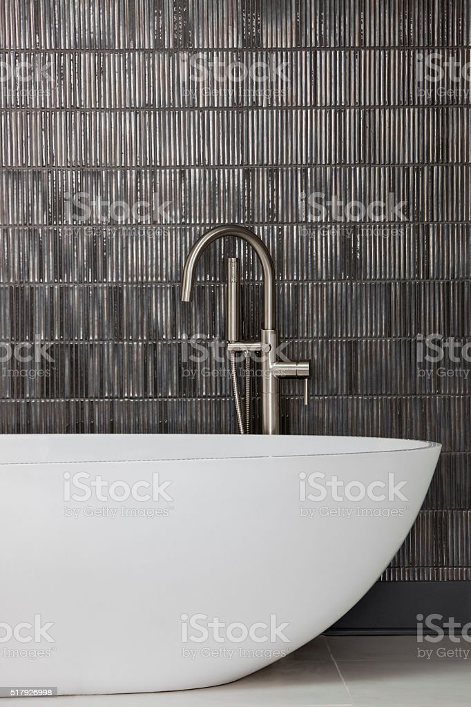 Modern bathtub and faucet with slate grey tiled wall stock photo