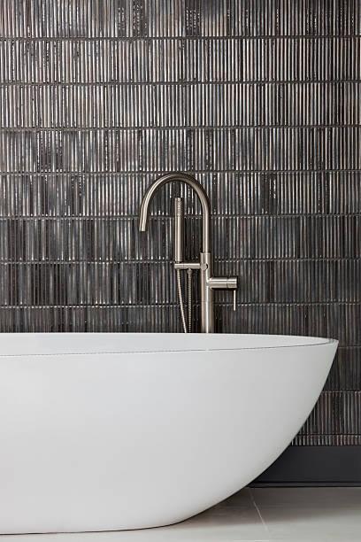 moderne badewanne und wasserhahn und schiefergrau gefliesten wand - minimalbadezimmer stock-fotos und bilder