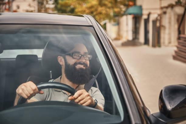 een moderne bebaarde man autorijden - voorruit stockfoto's en -beelden