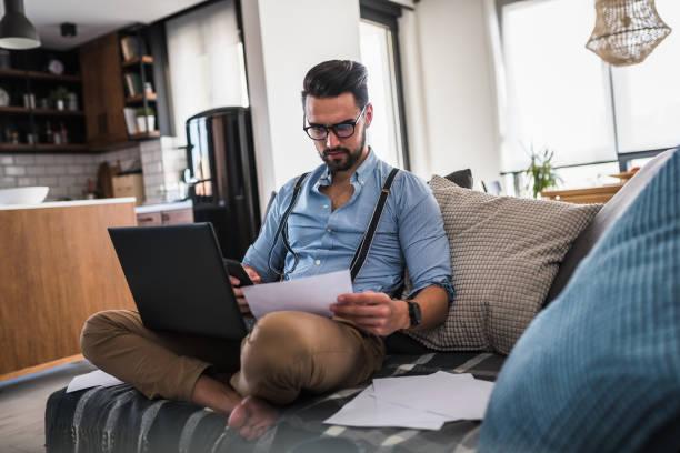 Modern Bearded jungen Geschäftsmann, der auf dem Laptop-Computer arbeitet, während er zu Hause auf dem Sofa sitzt und sich einige Dokumente anschaut – Foto