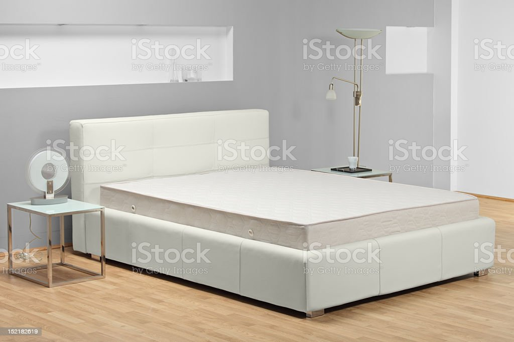 Modern bed with no sheets in a bedroom stock photo