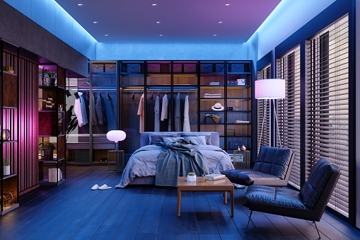Modern Bedroom Interior At Night With Neon Light. Messy Bed, Clothes In Closet, Armchairs And Floor Lamp.