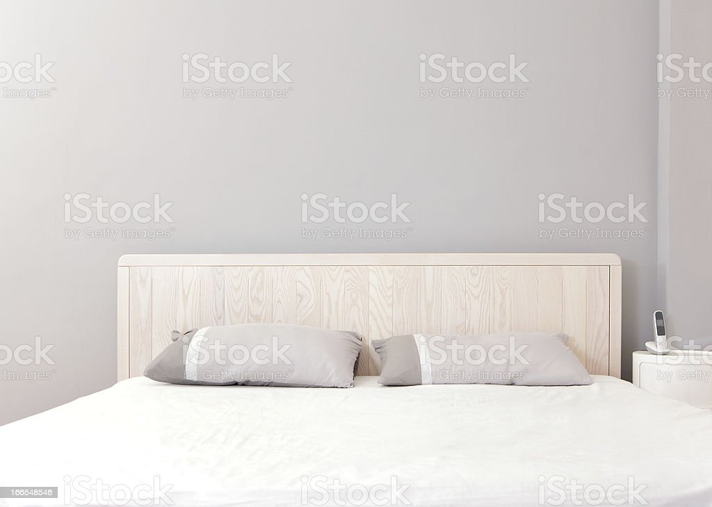 Modern bedroom styled with pale wood and greys stock photo