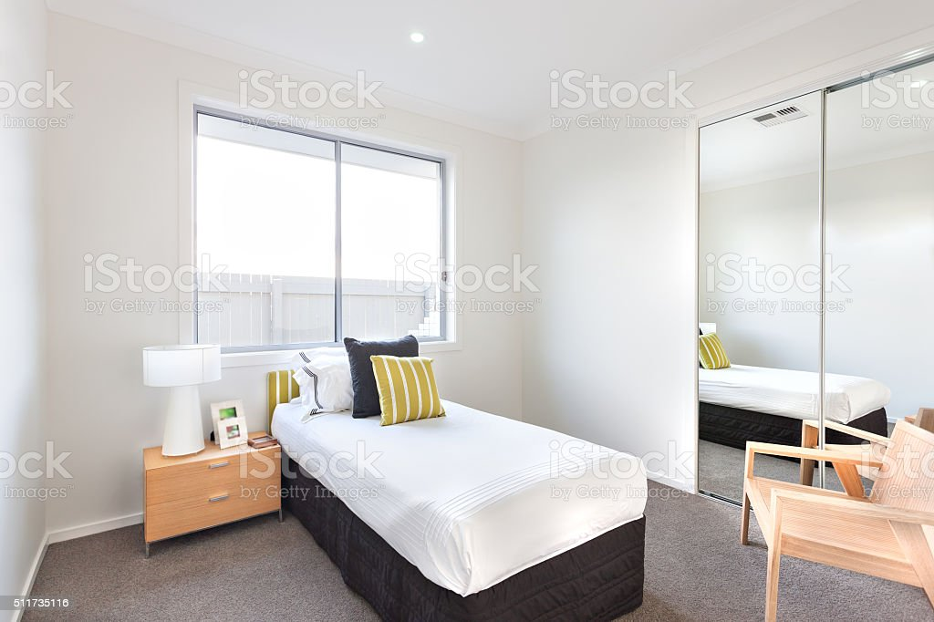 Modern bedroom with a single bed and white sheets stock photo