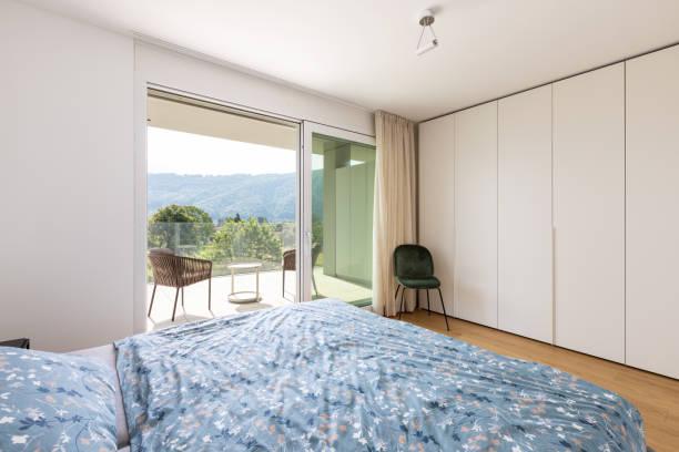 Modernes Schlafzimmer mit Bett und Samtstuhl – Foto