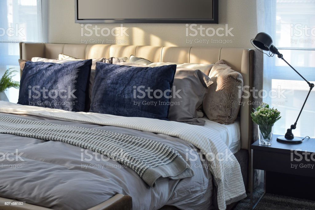 modern bedroom with blue pillows and black lamp on table stock photo