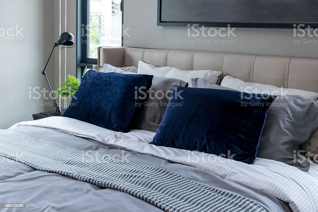 modern bedroom with blue pillows and black lamp stock photo