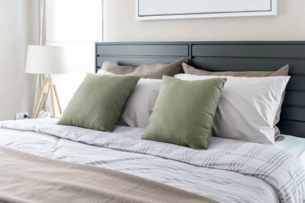 moderne schlafzimmer mit grüne kissen auf dem bett - kissen grün stock-fotos und bilder