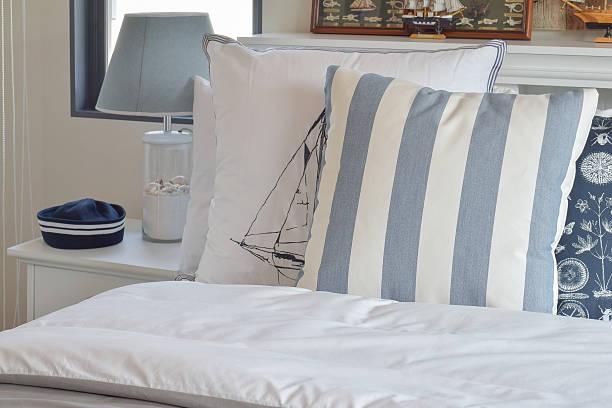 modern bedroom with green striped pillow on bed - nautisches schlafzimmer stock-fotos und bilder