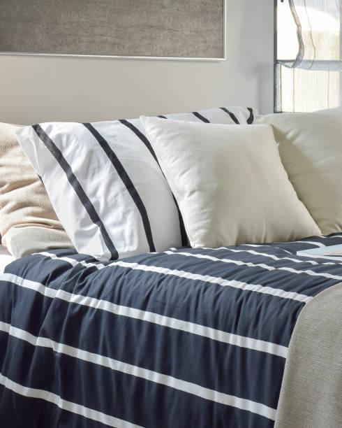 moderne schlafzimmer mit streifenmuster bettwäsche - marineblau schlafzimmer stock-fotos und bilder
